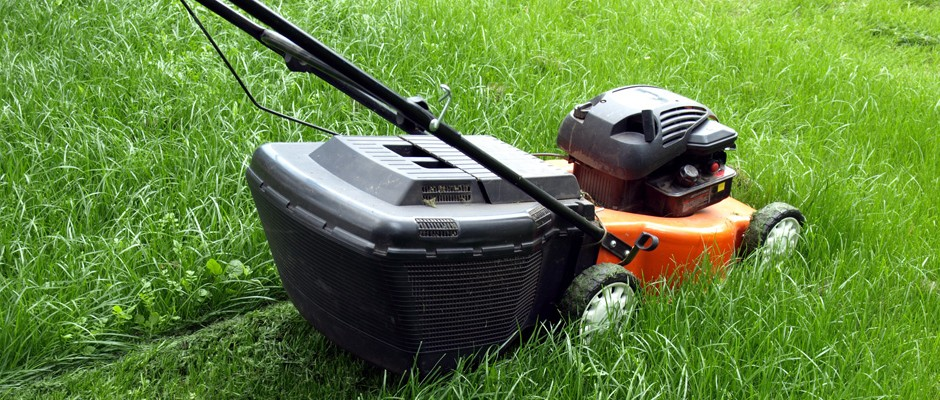large orange petrol mower cutting lush green grass